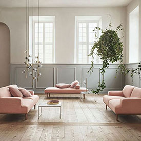 Boila Maison & Objet pink couches with wood flooring and a large hanging plant