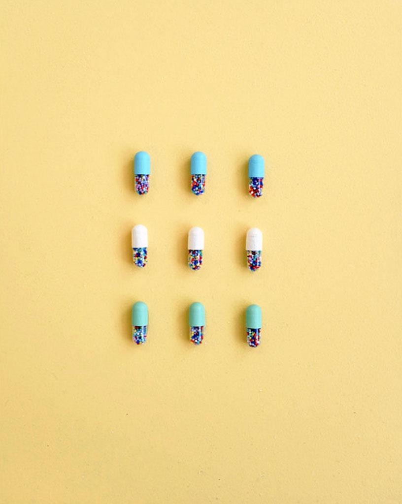 Reagan Corbett mixed media artwork of pills on a yellow background